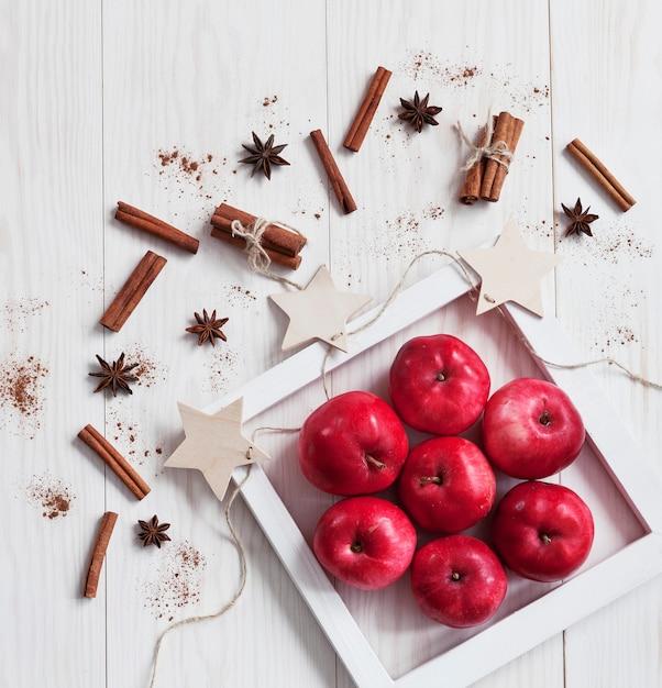 Manzanas rojas, canela y anice sobre fondo blanco de madera. Foto Premium