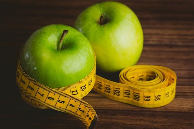Manzanas verdes con cinta métrica. Foto Premium