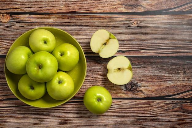 Manzanas verdes en un cuenco de cerámica verde, vista superior   Foto Gratis