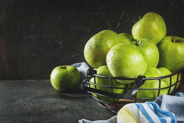 Manzanas verdes de granja orgánica cruda fresca en cesta de metal negro, oscuro oxidado, copyspace Foto Premium