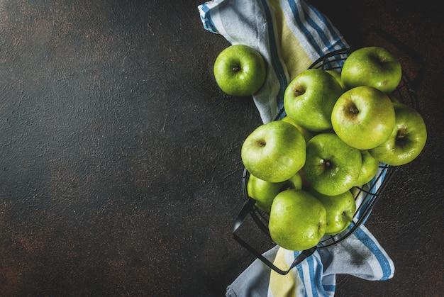 Manzanas verdes de granja orgánica cruda fresca en cesta de metal negro, oxidado oscuro, vista superior de copyspace Foto Premium