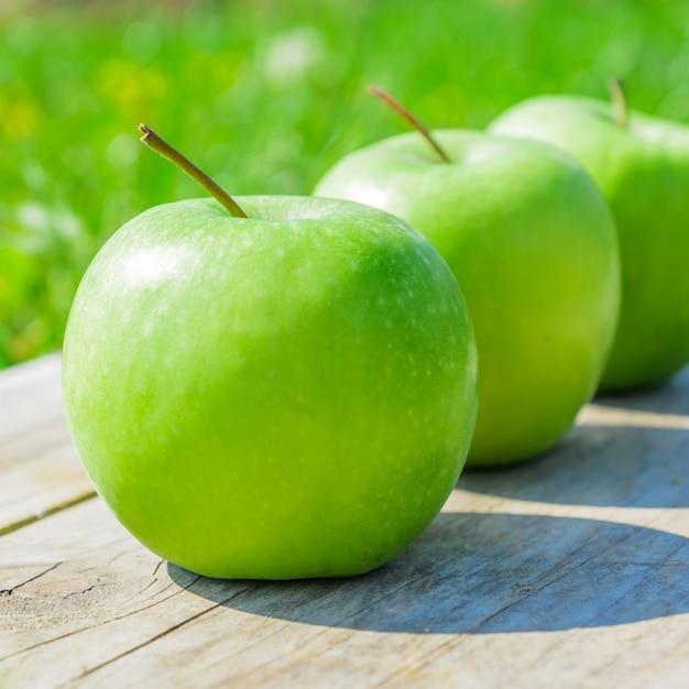 Manzanas verdes recién cortadas en mesa de madera sobre hierba verde Foto Premium