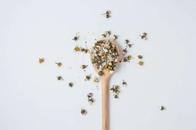 Manzanilla seca en una cuchara, vista superior Foto gratis