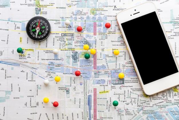 Mapa marcado con alfileres y una brújula. Foto gratis