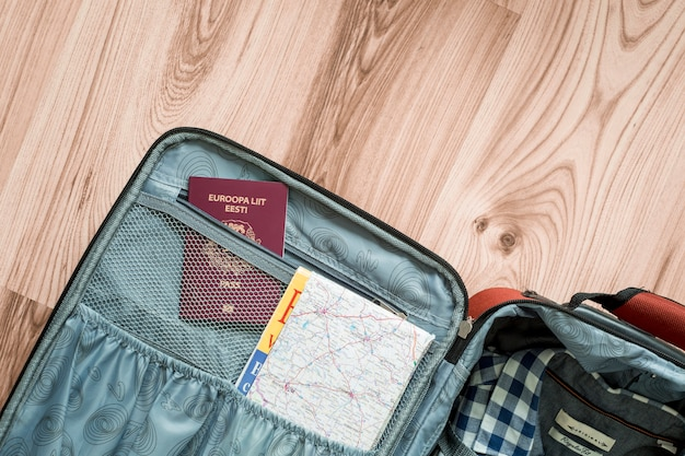 Mapa y pasaporte en maleta Foto gratis