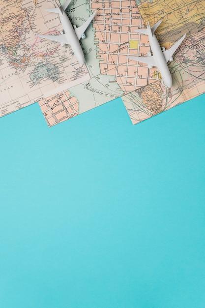 Mapas y aviones de juguete sobre fondo azul. Foto gratis