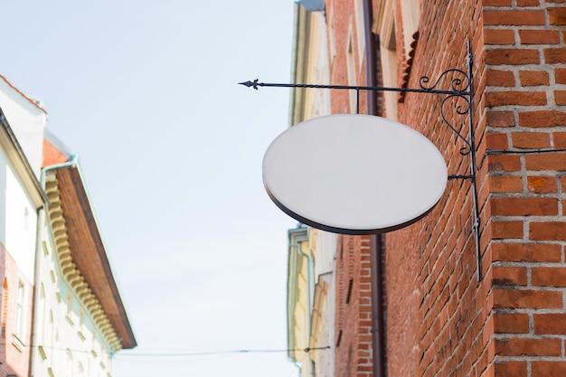Maqueta de un círculo vintage ovalado vacío en blanco blanco para cafetería, nombre y logotipo del restaurante, en una ciudad vieja Foto Premium