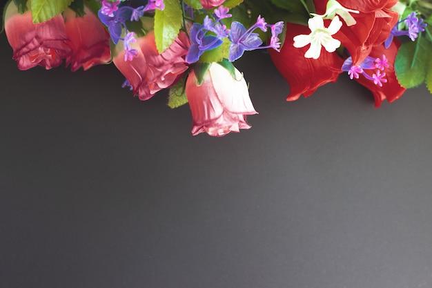 Maqueta conmemorativa con flores artificiales sobre un fondo oscuro Foto Premium