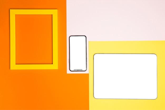 Maqueta de dispositivos de plano sobre fondo de colores Foto gratis