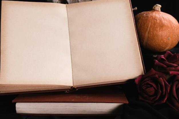 Maqueta de libro abierto con rosas y calabaza Foto gratis