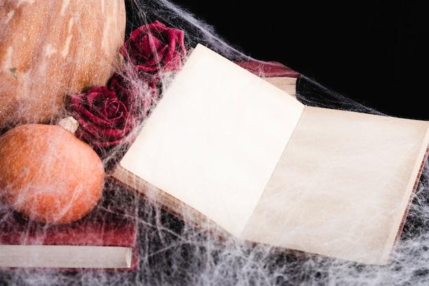 Maqueta de libro con tela de araña y calabazas Foto gratis