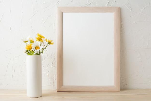 Maqueta de marco con manzanillas blancas y amarillas en florero Foto Premium