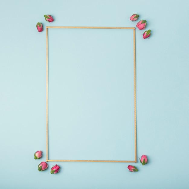 Maqueta marco vacío con capullos de rosa sobre fondo azul. Foto gratis