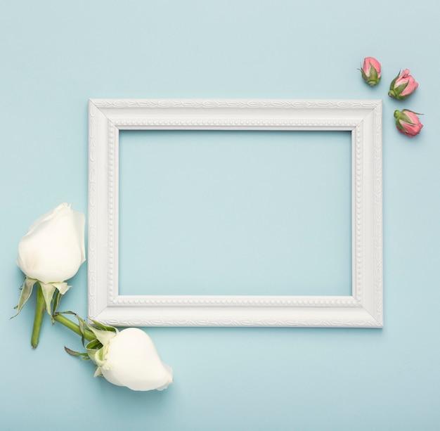 Maqueta marco vacío horizontal blanco con capullos de rosa sobre fondo azul. Foto gratis