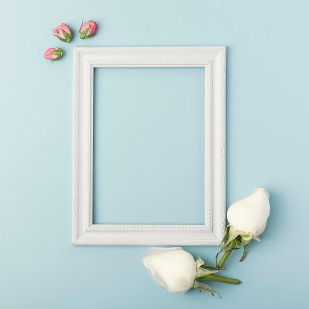 Maqueta marco vacío vertical blanco con capullos de rosa sobre fondo azul. Foto gratis