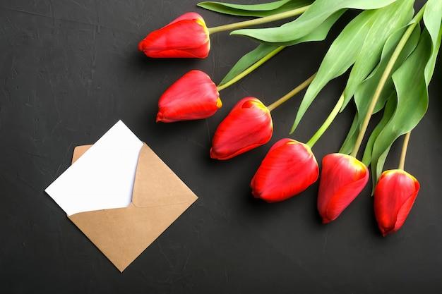 Maqueta del ramo de tulipanes rojos frescos y tarjeta de felicitación en sobre kraft Foto Premium