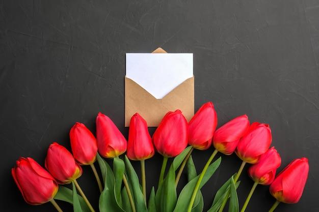 Maqueta del ramo de tulipanes rojos frescos y tarjeta de felicitación vacía blanca en sobre kraft Foto Premium
