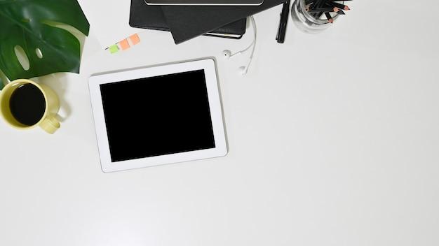 Maqueta de tableta blanca, café y suministros de oficina en la mesa de escritorio de oficina. Foto Premium