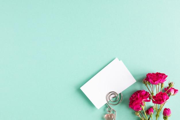 Maqueta de tarjetas de visita sobre un fondo de color y una flor rosa, copyspace, topview. Foto gratis