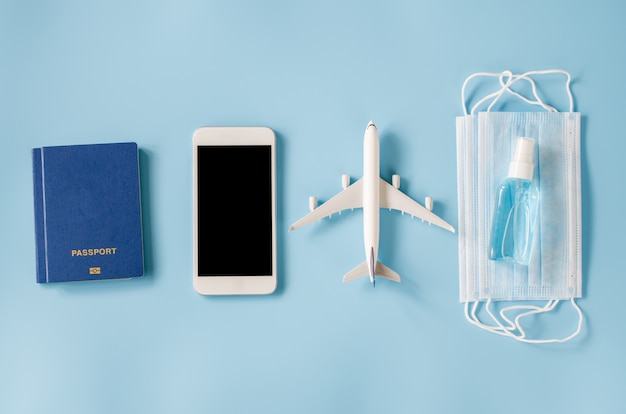 Maqueta de teléfono inteligente con modelo de avión, pasaportes, mascarilla y spray desinfectante para manos Foto Premium