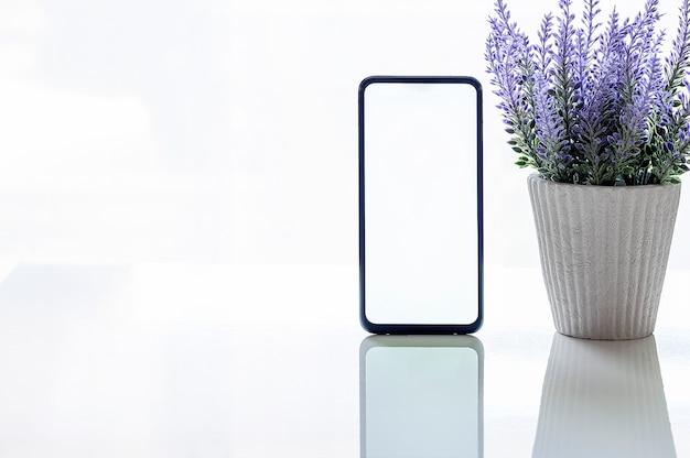 Maqueta de teléfono inteligente con pantalla en blanco y planta de interior en la mesa superior blanca Foto Premium