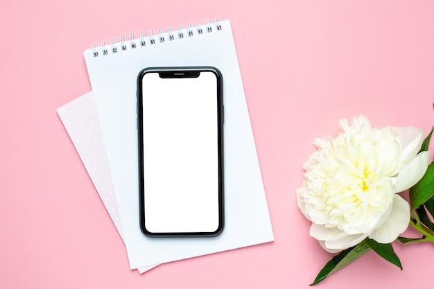 Maqueta de teléfono móvil, cuaderno y flor de peonía en mesa de color rosa pastel. escritorio de trabajo de mujer color de verano Foto Premium