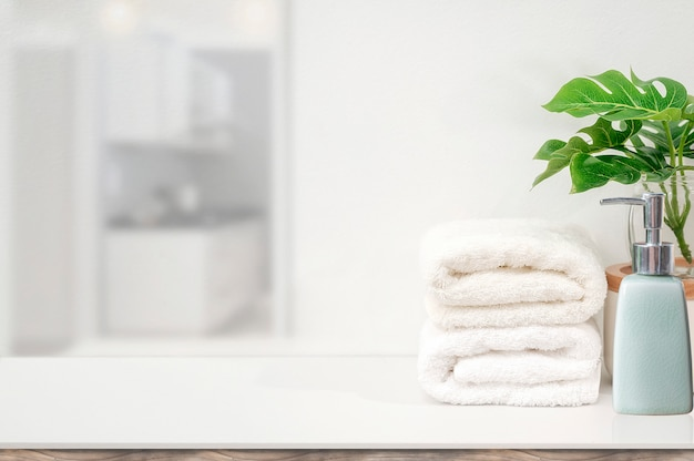 Maqueta de toallas blancas y planta de interior en la mesa blanca con espacio de copia para la visualización del producto. Foto Premium