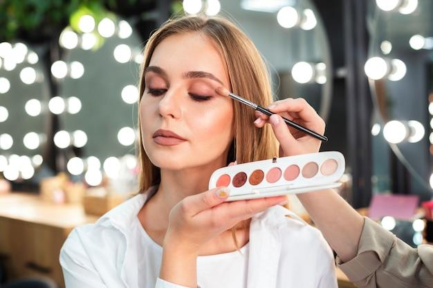 Maquilladora aplicando sombra de ojos a mujer con pincel Foto gratis