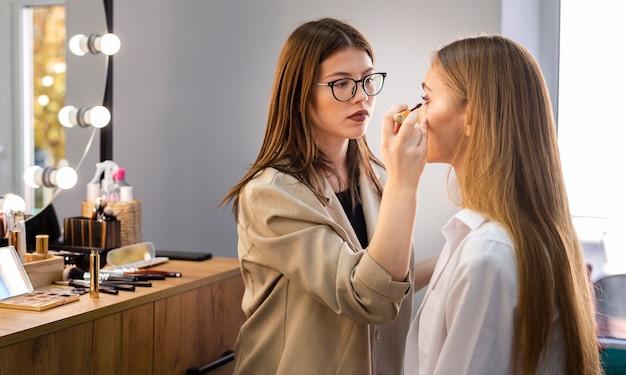 Maquilladora concentrada aplicando rimel en mujer Foto gratis