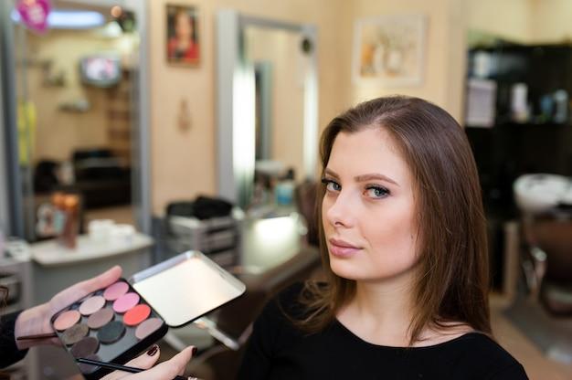 Maquilladora hace maquillaje de niña hermosa Foto Premium