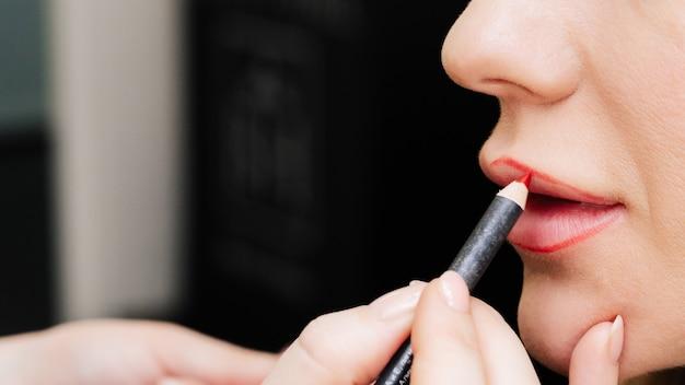 Maquilladora pinta los labios con un lápiz labial a una mujer en un salón de belleza Foto Premium