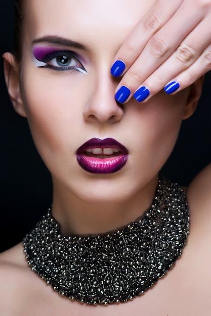 Maquillaje de belleza. maquillaje morado y uñas brillantes de colores Foto Premium