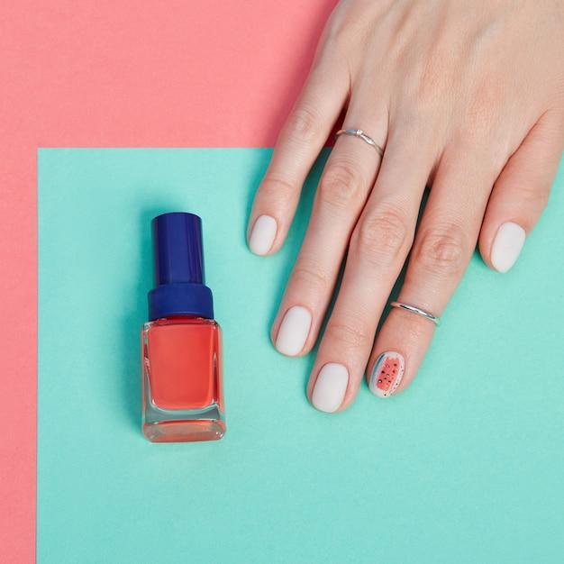 Maquillaje cosmético para manos, manicura de uñas hermosas, esmalte de uñas, publicidad en papel de color Foto Premium