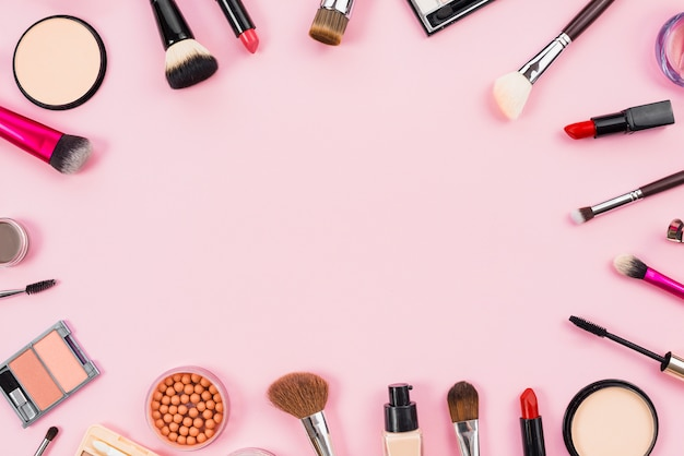 Maquillaje cosméticos, pinceles y otros elementos esenciales sobre fondo rosa. Foto gratis