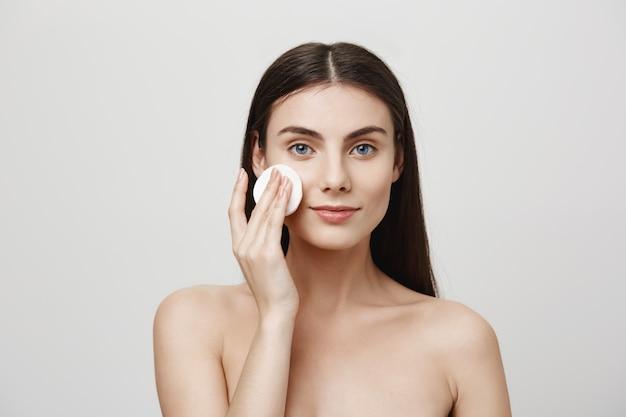 Maquillaje de despegue de mujer linda sonriente con algodón Foto gratis