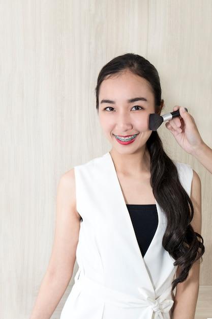 Maquillaje hermoso joven de la prueba de la mujer con la cara para enviar. Foto Premium