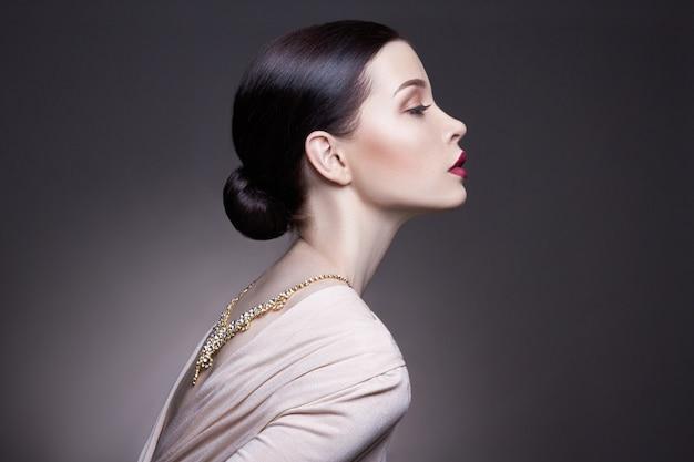 Maquillaje profesional de la mujer morena joven del retrato Foto Premium