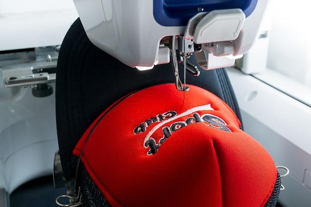 Máquina de bordar y gorra deportiva de cerca la imagen Foto Premium