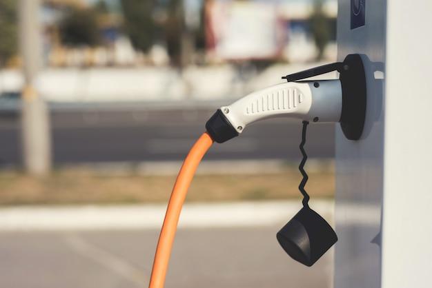 La máquina eléctrica se detuvo en la estación de carga para recargarse. Foto Premium