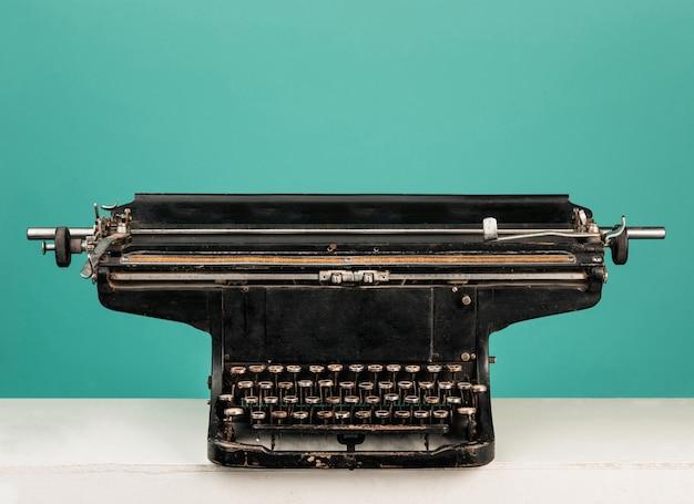Máquina de escribir antigua retro con papel sobre mesa de madera Foto gratis
