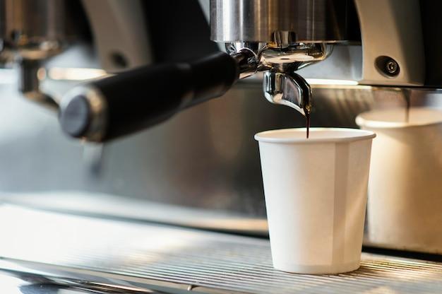 Máquina vertiendo café en vaso desechable Foto gratis