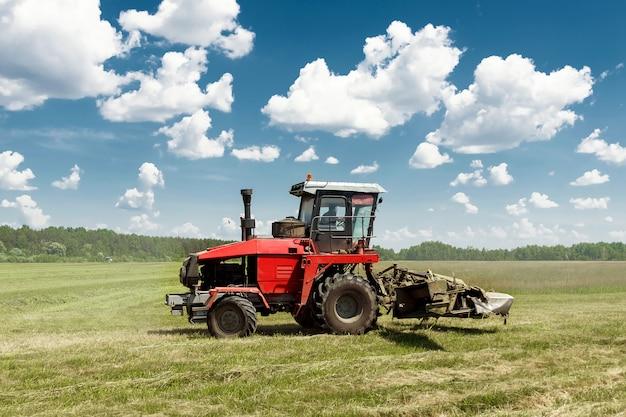 Maquinaria agrícola, cosechadora cortando césped en un campo contra un cielo azul. Foto Premium