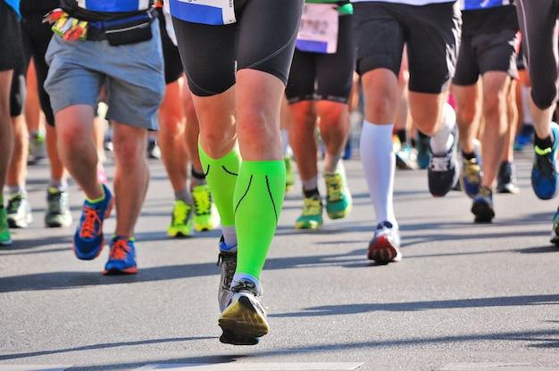 Maratón carrera, pies de corredores en carretera, deporte, fitness y concepto de estilo de vida saludable Foto Premium
