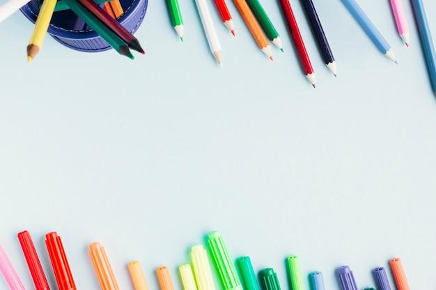 Marcadores brillantes y lápices sobre fondo blanco Foto gratis
