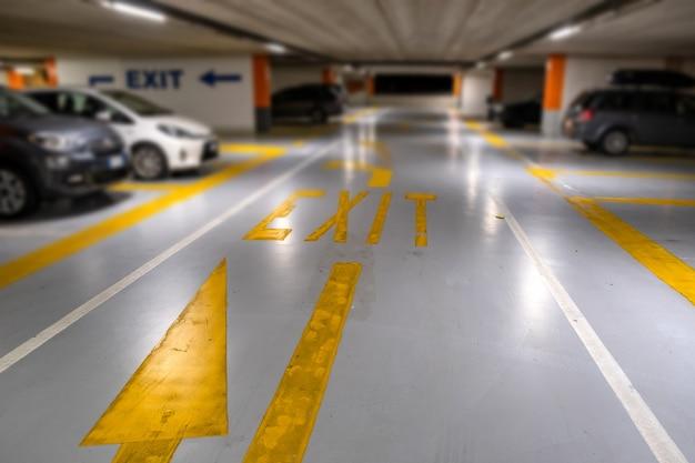 Marcas amarillas con coches modernos borrosos estacionados dentro de un estacionamiento subterráneo cerrado. Foto Premium