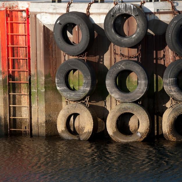 Marcas marcadas con mareas colgadas en un muelle al lado de una escalera hasta el agua Foto Premium