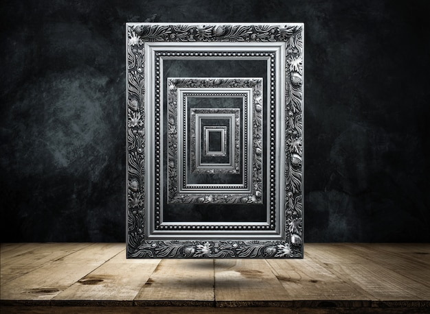 Marco antiguo de plata en la pared oscura del grunge con la parte superior de la mesa de madera misteriosa, confusa, fondo Foto Premium