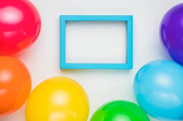 Marco azul y globos de colores en superficie blanca Foto gratis