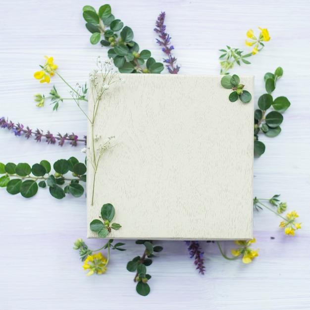 Marco en blanco blanco de madera debajo de las flores y hojas sobre fondo con textura Foto gratis
