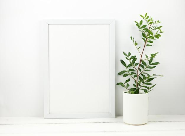 Marco blanco en blanco y planta en maceta en mesa de madera blanca Foto gratis